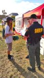 Hippy talking haircuts with bald Sheriff